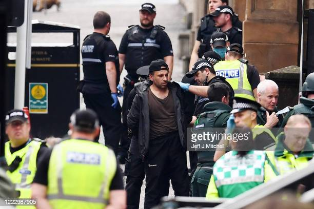 Police officers speak to a man at the scene after there were initial reports of three people being killed in a central Glasgow hotel on June 26, 2020...