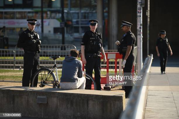 Police officers speak to a man sitting down in Piccadilly Gardens in the centre of Manchester north west England on March 27 2020 Britain was under...