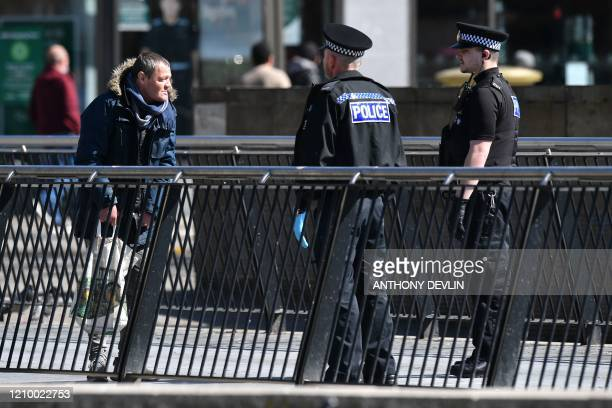 Police officers speak to a pedestrian in Piccadilly Gardens in the neardeserted city centre of Manchester northwest England on April 15 during the...