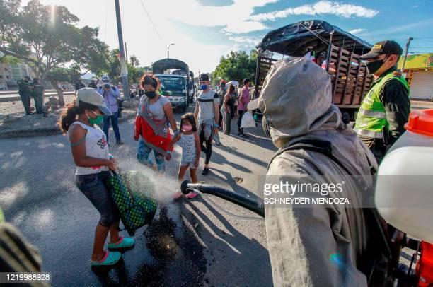 Police officers spray disinfectant on Venezuelans and their baggage as they are being transferred from the Simon Bolivar international crossing point...