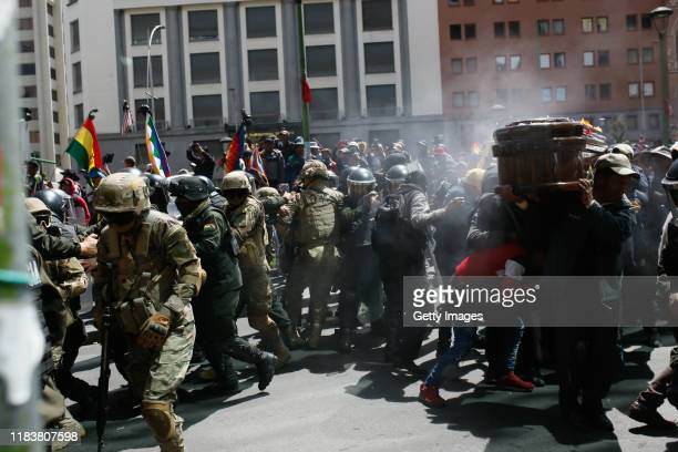 Police officers spray tear gas as a group of people carry a coffin of one of the victims killed during clashes with police at the Senkata fuel plant...