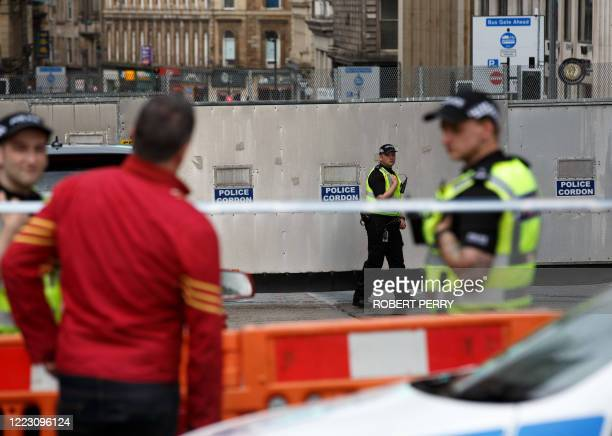 Police officers staff a cordon in central Glasgow on June 27 2020 following a stabbing incident at the Park Inn hotel the previous day Scottish...