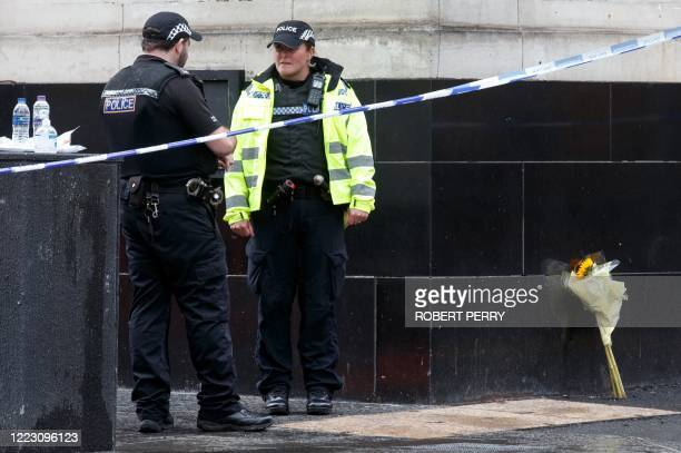 Police officers staff a cordon where a bunch of flowers has been left in central Glasgow on June 27 2020 following a stabbing incident at the Park...