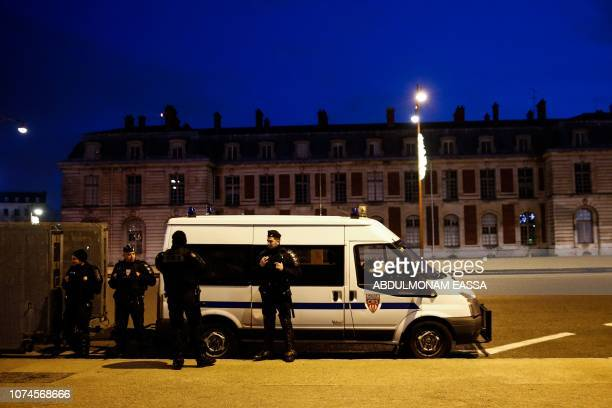 Police officers stand at dawn next to a police truck as 'Yellow Vest' protestors plan to demonstrate in front of the Chateau de Versailles in...