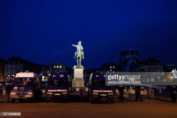Police officers stand at dawn next to a statue of French monarch Louis XIV as 'Yellow Vest' protestors plan to demonstrate in front of the Chateau de...
