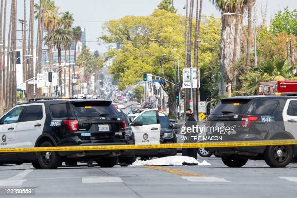 Police officers stand at the corner of Fairfax Avenue and Sunset Boulevard where a body covered in a white sheet lies on the pavement in Los Angeles...