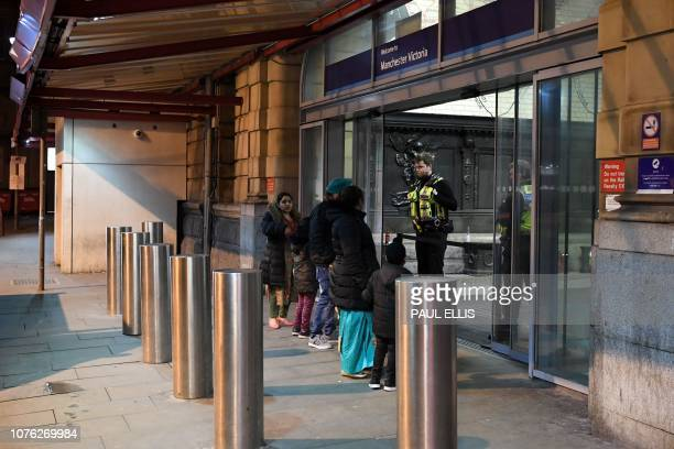 Police officers stand at the entrance to Manchester Victoria Station in Manchester on January 1 following a stabbing on December 31 2018 A man a...