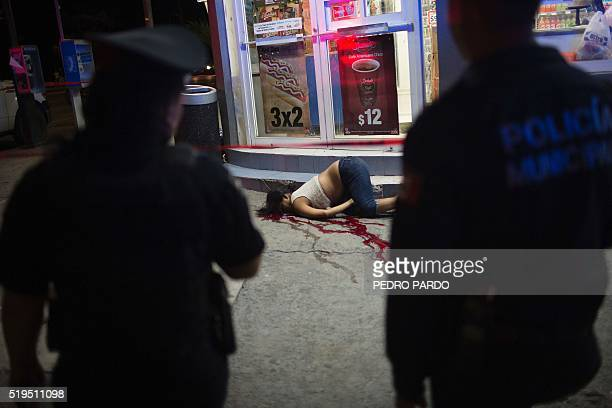 Police officers stand at the scene where a woman was killed on a street of Acapulco Guerrero State Mexico on April 6 2016 Guerrero is one of Mexico's...