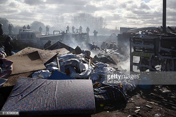 Police officers stand behind a destroyed tent as part of the 'jungle' migrant camp is cleared on February 29 2016 in Calais France The French...