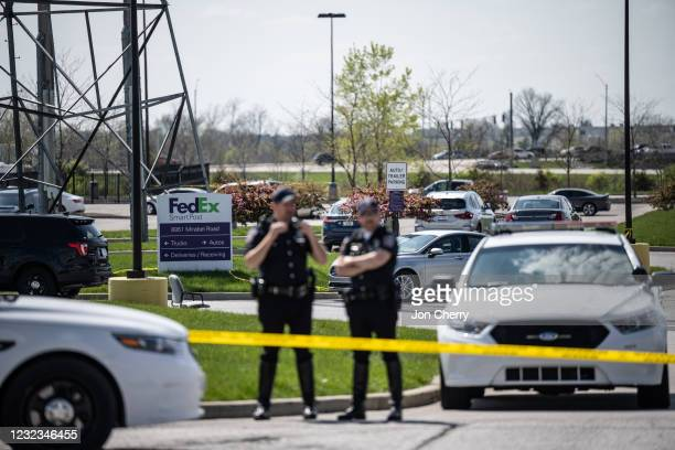 Police officers stand behind caution tape near a crime scene on April 16, 2021 in Indianapolis, Indiana. The area is the scene of a mass shooting at...