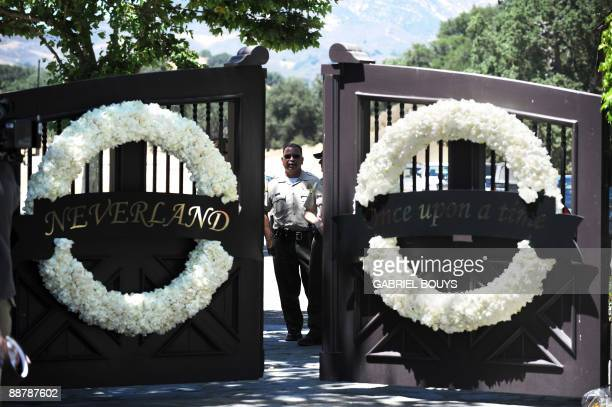 Police officers stand behind the closed gate of Michael Jackson's Neverland ranch in Los Olivos, California on July 01, 2009 in Los Angeles,...