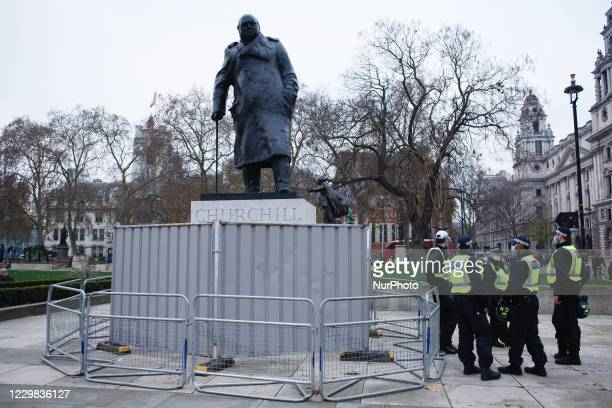 Police officers stand beside the Parliament Square statue of Britain's wartime prime minister Winston Churchill, barricaded by metal fencing during a...