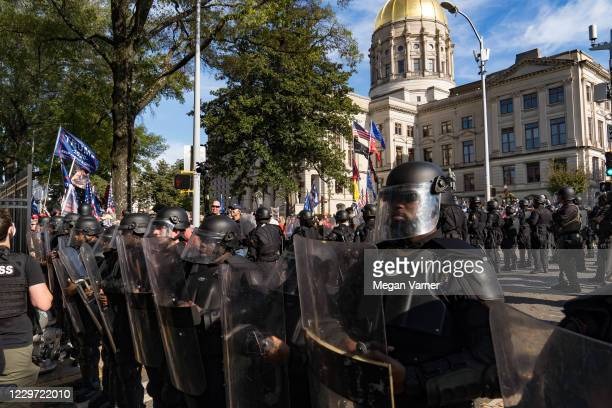 Police officers stand between counter protestors and supporters of Donald Trump during a 'Stop the Steal' protest outside of the Georgia State...