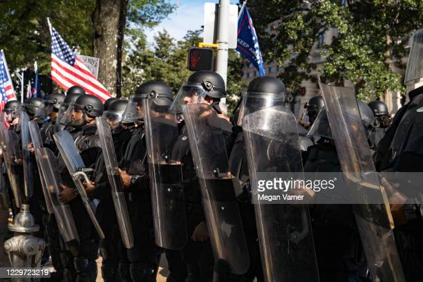 Police officers stand between protesters and counter-protesters after blocking off an intersection as supporters of Donald Trump host a 'Stop the...