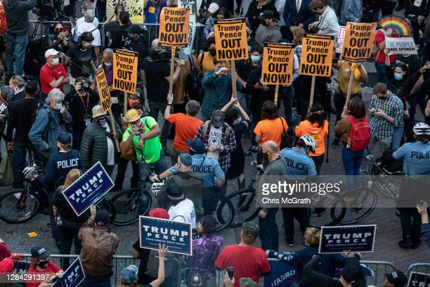 Police officers stand between protesters supporting U.S. President Donald Trump and people participating in a protest in support of counting all...