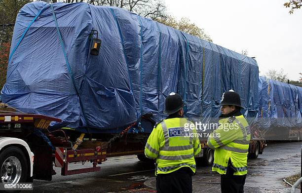 Police officers stand by as tram carriages covered in tarpaulin are driven away on trucks in Croydon south Lodnon on November 12 2016 At least seven...