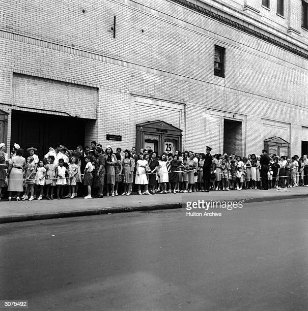 Police officers stand by to make sure that patrons lined up for a movie theater don't get unruly 1939