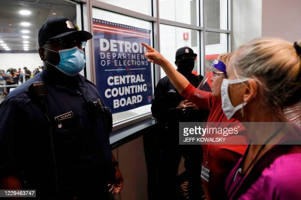 Police officers stand facing supporters of US President Donald Trump as they chant slogans outside the room where absentee ballots for the 2020...