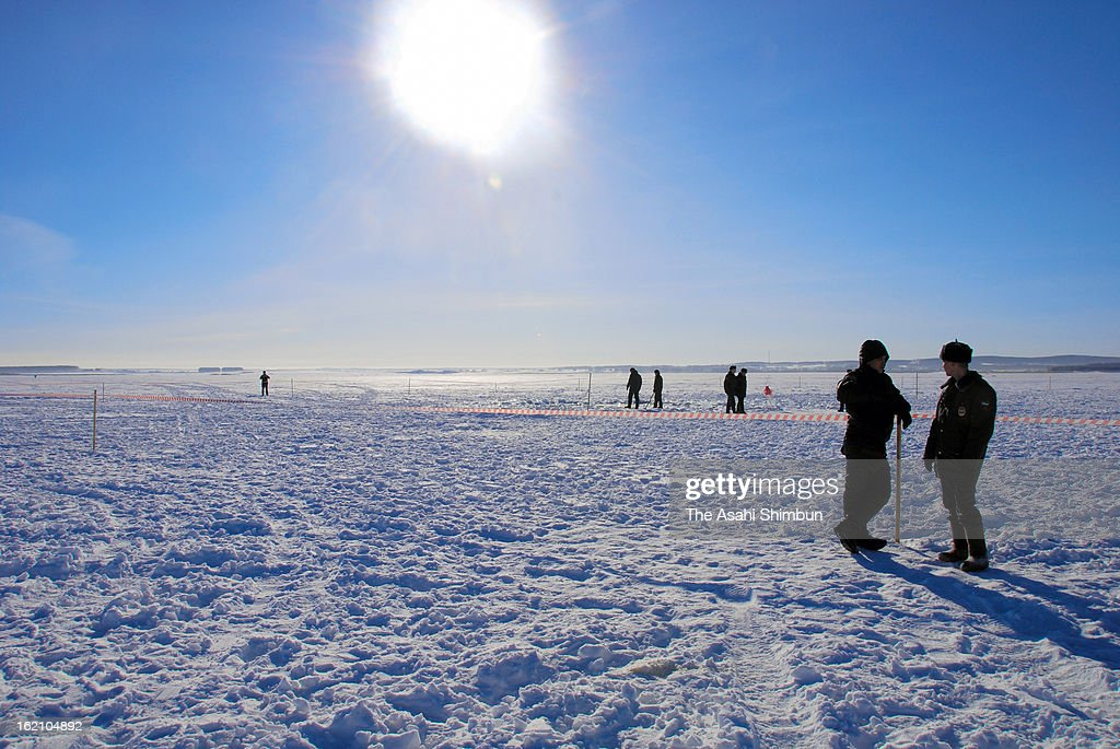 Police officers stand guard a hole in the ice of Chebarkul Lake on March 16, 2013 some 80 kilometers from Chelyabinsk, Russia. Local government reported more than 1,100 people injured, mostly by flying glass broken by the shock wave of the meteor explosion.