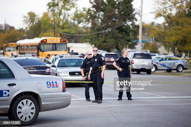 Police officers stand guard after a shooting incident at Fern Creek High School September 30 2014 in Louisville Kentucky Police say a male suspect...