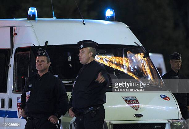 Police officers stand guard after the evacuation of the Eiffel Tower and the park surrounding the Paris landmark following a bomb alert on September...
