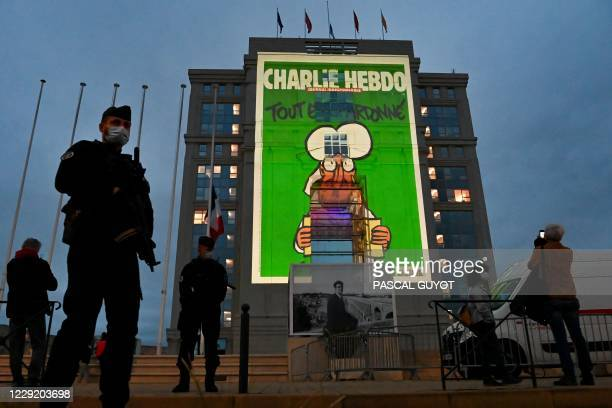 Police officers stand guard as cartoons of French satirical weekly newspaper Charlie Hebdo are projected onto the facade of the Hotel de Region in...