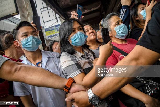 Police officers stand guard as Filipinos hoping to buy face masks crowd outside a medical supply shop that was raided by police for allegedly...