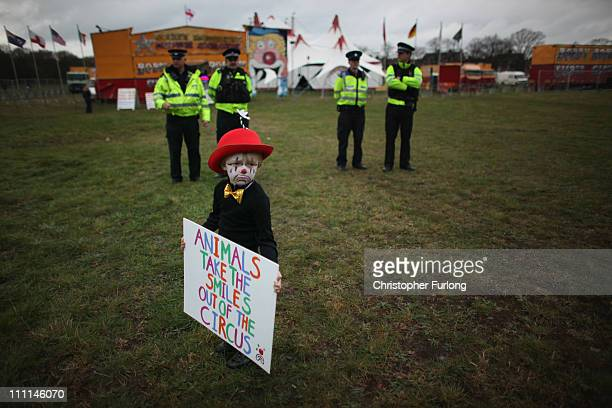 Police officers stand guard as fouryearold Gabriel Ryan takes part in a protest outside Bobby Roberts Circus on Knutsford Common on March 30 2011 in...