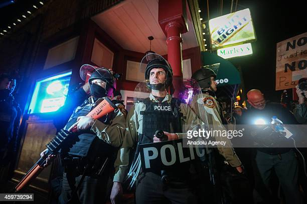 Police officers stand guard as people gather in front of the Ferguson Police Department on November 29 2014 to protest against the Grand Jury's...