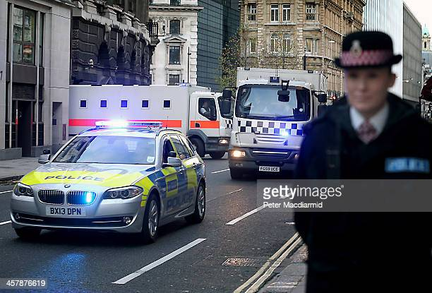 Police officers stand guard as prison vans leave The Old Bailey on December 19 2013 in London England Michael Adebolajo and Michael Adebowale have...
