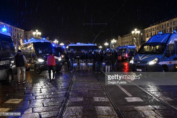 Police officers stand guard as protesters gather during an anti government demonstration on October 26 2020 in Turin Italy Following a surge in new...