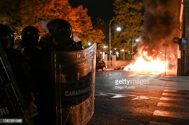 Police officers stand guard as protesters set fire to public property during an anti government demonstration on October 26 2020 in Turin Italy...