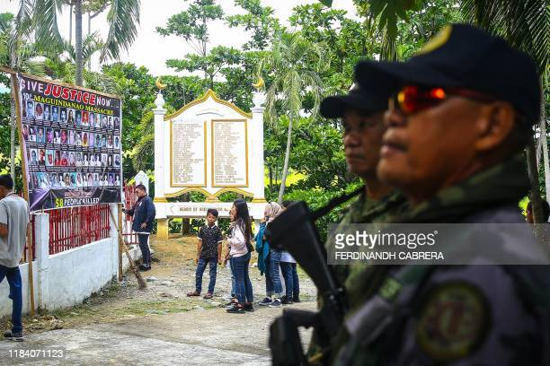 Police officers stand guard as relatives of the 58 people slain in the country's worst political massacre visit the site of the massacre in Ampatuan...