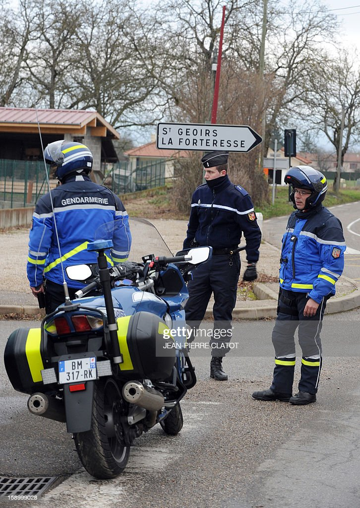Police officers stand guard as they block access to the site of a small plane crash in Saint-Geoirs, on January 5, 2013. Five people died when their private plane crashed a few moments after taking off from the Grenoble airport in southeastern France, local police said. AFP PHOTO / Jean Pierre Clatot