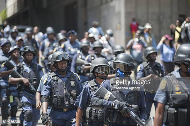 Police officers stand guard as university students stage a protest against the raise on tuition fees in Johannesburg South Africa on October 12 2016