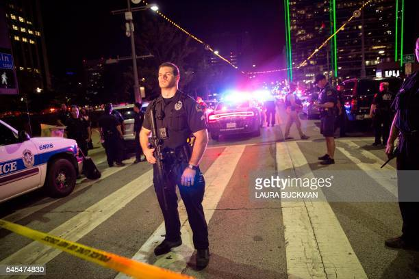 TOPSHOT Police officers stand guard at a baracade following the sniper shooting in Dallas on July 7 2016 A fourth police officer was killed and two...