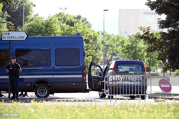 Police officers stand guard at a cordon in SaintQuentinFallavier on June 27 2015 at the site where a decpaitated body was discovered following a...