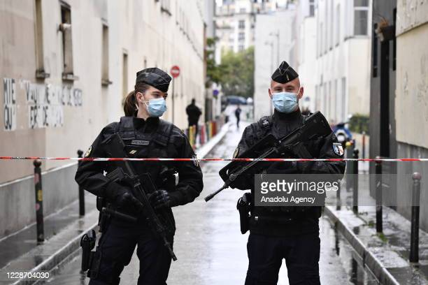 Police officers stand guard at a site after a knife attack near the former headquarters of satirical magazine Charlie Hebdo in Paris, France on...