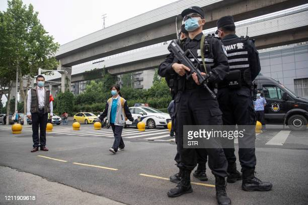 Police officers stand guard at an entrance of a high school as senior students enter school in Wuhan in China's central Hubei province on May 6 2020...