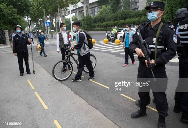 Police officers stand guard at an entrance of a high school as senior students enter the premises in Wuhan in China's central Hubei province on May...