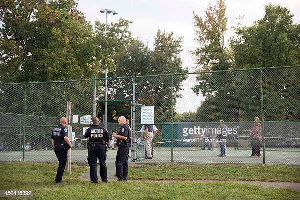 Police officers stand guard at Fern Creek Park where students gathered to be reunited with their parents following a shooting at Fern Creek High...