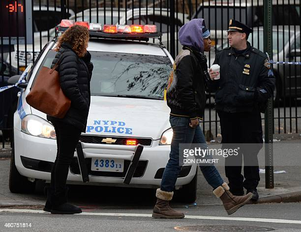 Police officers stand guard at the intersection of Tompkins Ave and Myrtle Ave December 21 2014 in New York near the site where two New York City...