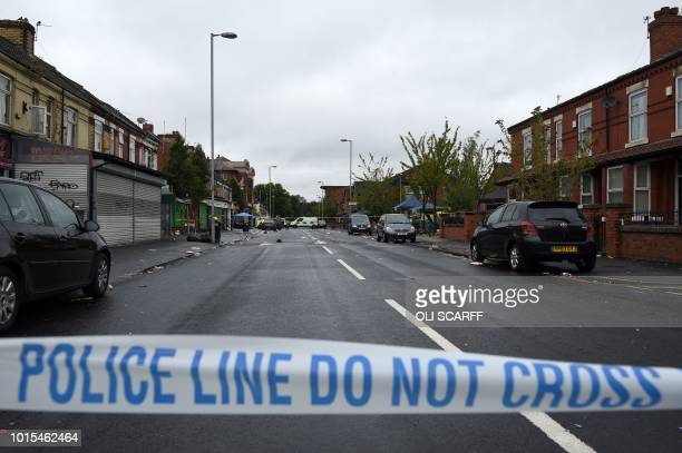 Police officers stand guard at the scene of a shooting at Claremont Road in the Moss Side neighbourhood of Manchester, on August 12, 2018. - Ten...