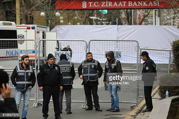 Police officers stand guard at the security perimeter around the scene of an explosion on March 14 2016 the day after a suicide car bomb ripped...