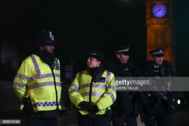 Police officers stand guard at Westminster Bridge with Elizabeth Tower in the background as spectators arrive to watch the New Year's Eve fireworks...