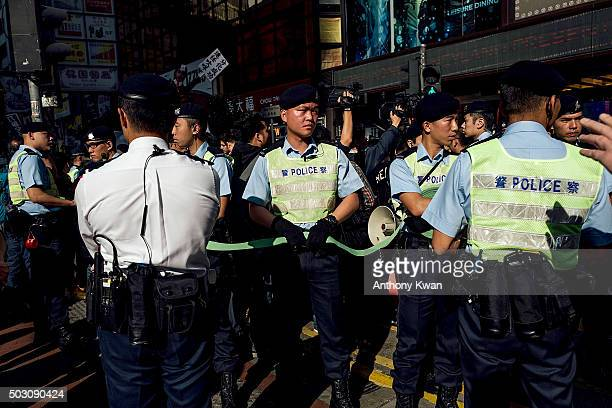 Police officers stand guard before the start of the New Year's Day Rally on January 1 2016 in Hong Kong Thousands of protesters took to the streets...