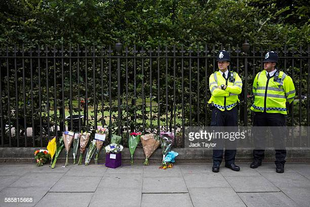 Police officers stand guard by flowers left at the scene of a knife attack in Russell Square on August 4 2016 in London England Six people were...