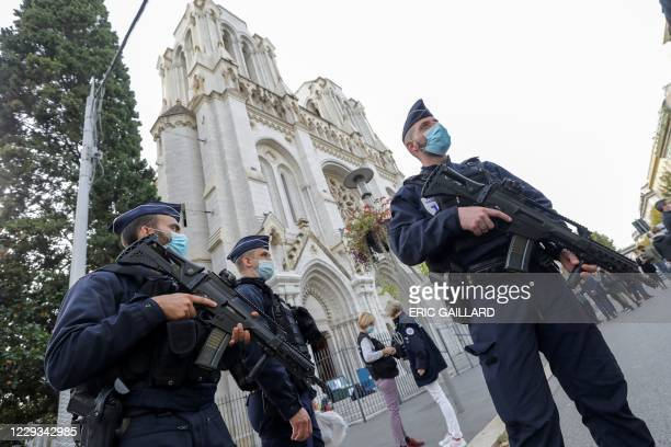 Police officers stand guard by the Notre-Dame de l'Assomption Basilica in Nice on October 29, 2020 after a knife-wielding man kills three people at...