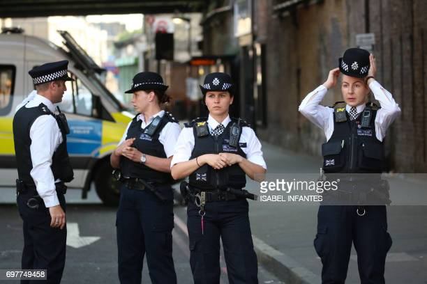 Police officers stand guard close to the scene of a van attack in Finsbury Park north London on June 19 2017 Ten people were injured when a van drove...