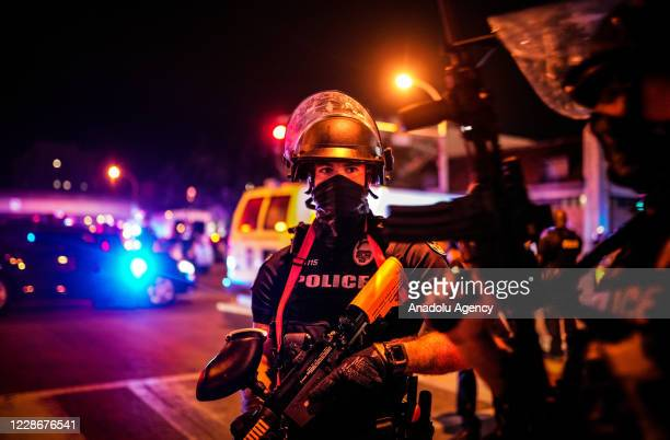 Police officers stand guard during a protest in Louisville, Kentucky, on September 23 after a judge announced the charges brought by a grand jury...